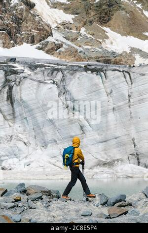 Homme mûr explorant le glacier en fusion tout en se tenant sur des rochers