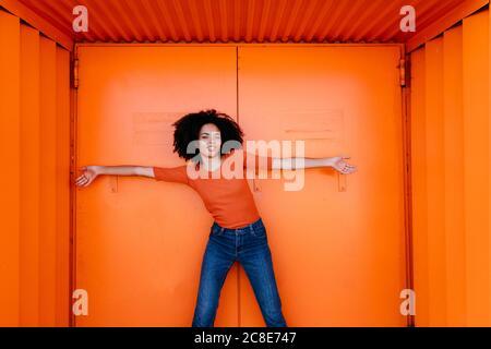 Jeune femme souriante debout avec les bras tendus contre le métal orange porte