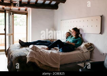 Couple regardant un film assis sur le lit à la maison