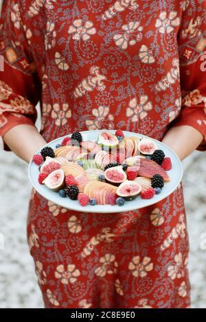 Gros plan de la jeune femme tenant des fruits dans l'assiette en se tenant debout à l'extérieur