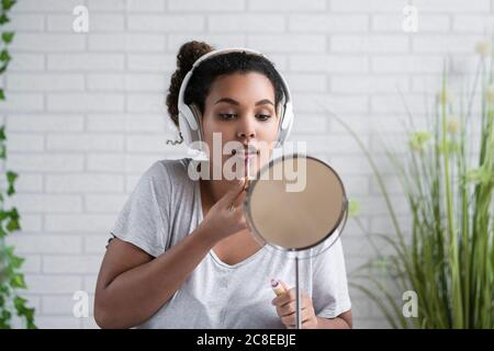 Une jeune femme écoute de la musique à l'aide d'un casque en appliquant un brillant à lèvres accueil Banque D'Images