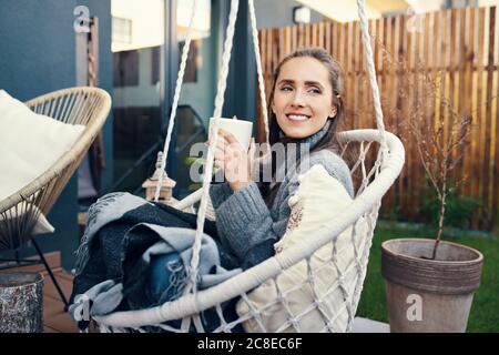 Jeune femme souriante tenant une tasse tout en se détendant sur la balançoire cour Banque D'Images