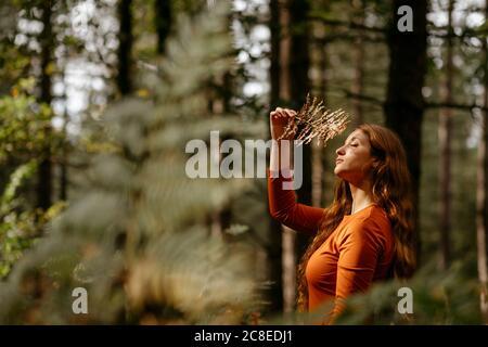 Jeune femme avec les yeux fermés tenant l'usine tout en se tenant contre arbres en forêt