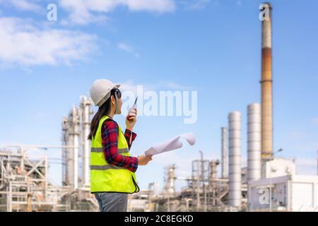 Femme asiatique technicien Ingénieur industriel utilisant walkie-talkie et tenant bluprint travaillant dans une raffinerie de pétrole pour l'étude de chantier de construction en ingénieur civil