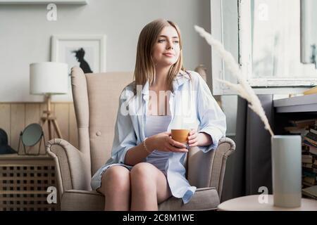 Belle jeune femme buvant du café et regardant par la fenêtre tout en étant assise dans un fauteuil à la maison.