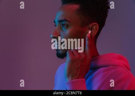 Portrait of african american man concentré en sweat coloré d'écouter de la musique avec earpod sur fond violet isolés