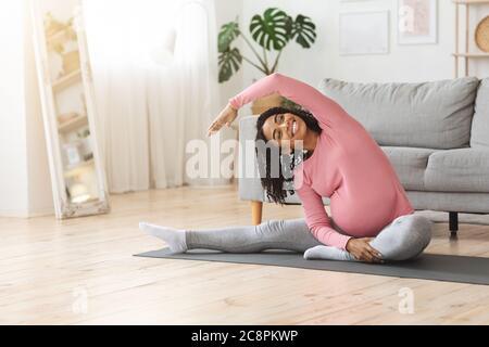 Femme enceinte africaine positive faisant de l'exercice matinal à la maison Banque D'Images