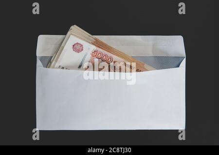 Grandes dénominations de 5000 roubles dans une enveloppe blanche. Main d'homme tient une enveloppe avec de l'argent. Le concept de corruption