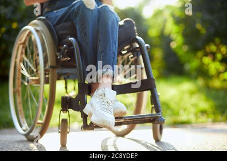 jeune fille handicapée en combinaison et baskets blanches assises avec des jambes croisées sur le fauteuil roulant. photo courte gros plan.