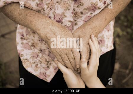Tenir les mains froissées d'une femme âgée et les jeunes mains d'une adolescente, concept d'âge, famille, soins et soutien à la famille, aînés Banque D'Images
