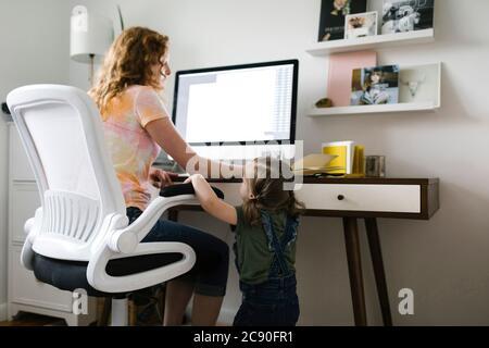 Fille (2-3) interrompant la mère au travail à la maison