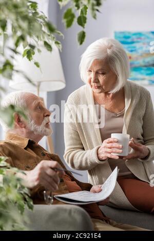 attention sélective de la femme senior tenant une tasse de thé tout en parlant à un mari surpris Banque D'Images