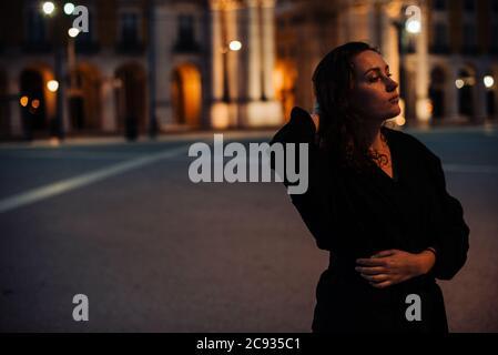 Portrait en demi-longueur de la jeune femme vêtue de noir, debout seule dans la rue. Nuit, lumière de la rue, contemplatif Banque D'Images
