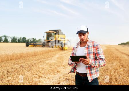 Agriculture de précision. Tablette de maintien pour les exploitants agricoles pour le guidage et le contrôle des moissonneuses-batteuses avec système d'automatisation moderne. Agronome utilisant des données en ligne