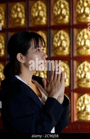 Khai Doan King honore la pagode. Femme priant dans le temple. Buon Me Thuot. France.