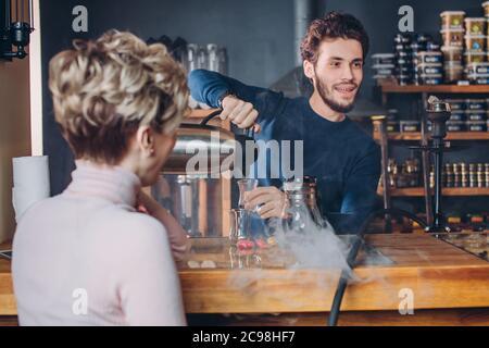 traditions et personnes. Boisson turque. Bardak. Jeune agréable serveur heureux versant du thé dans le verre. Gros plan.
