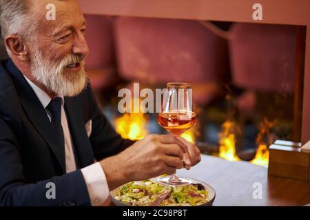 Homme à la barbe et aux cheveux gris en smoking avec verre de champagne, assis au restaurant et rire, regardez la personne en face. Contexte firemplacer