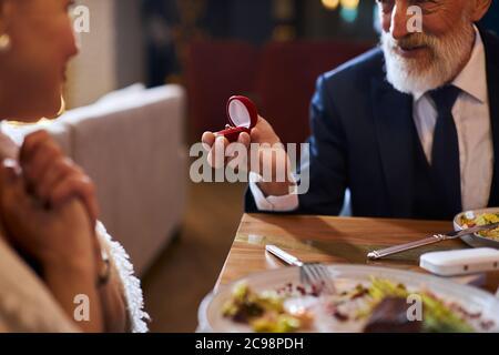 Vous me marierez. Proposition de mariage Senior l'homme Senior semble heureux femme en attente de réponse à la proposition de mariage. Élégant homme en costume sourire bague de maintien, Banque D'Images