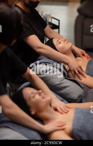 deux femmes d'âge moyen caucasien aiment les procédures de beauté, le massage de soulèvement de visage, ils veulent une peau lisse sans rides, massage anti-vieillissement sur le cou et le sh