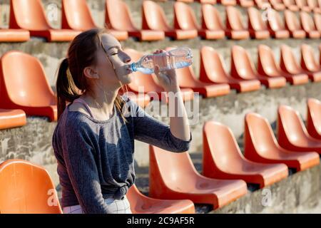 Jeune fille sportive attrayante dans les vêtements de sport se détendre après l'entraînement dur s'asseoir et boire de l'eau de la bouteille de sport spéciale après avoir courir sur un stade