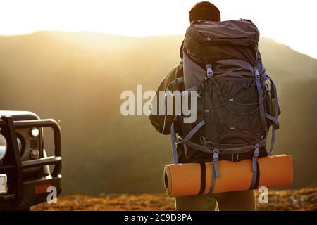 Portrait d'un jeune homme voyageur dans un équipement de randonnée se tenant près de sa voiture tout-terrain Banque D'Images