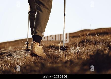 Homme voyageur avec des bâtons de trekking en haut de la montagne