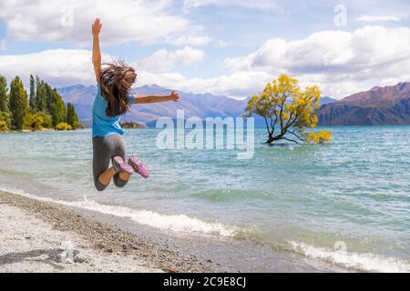 Voyage en Nouvelle-Zélande heureuse femme touristique saut de joie au paysage du lac de Wanaka avec un arbre solitaire, célèbre attraction. Banque D'Images