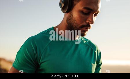Gros plan d'un athlète debout à l'extérieur avec un casque. Homme de fitness écoutant de la musique pendant la course.