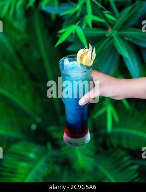Femme tenant un cocktail bleu avec fond vert