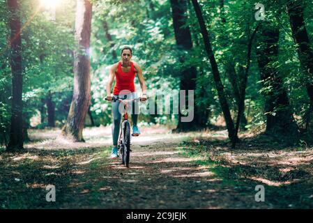 Femme à vélo dans le parc.