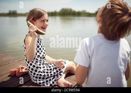 Frère et sœur faisant des blagues sur le quai du lac Banque D'Images