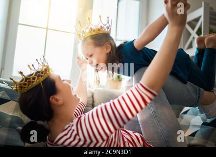 Famille heureuse et aimante. Mère et sa fille fille fille fille jouant et embrassant à la maison. Banque D'Images