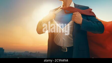Superhero businessman looking at city skyline at sunset. Le concept de la réussite, le leadership et la victoire dans les affaires. Banque D'Images