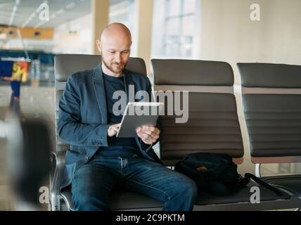 Beau adulte chauve barbu homme d'affaires en costume utilisant une tablette dans le salon de l'aéroport Banque D'Images