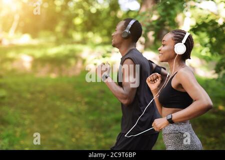 Concept de course matinale. Black sportif Homme et Femme jogging en plein air dans le parc
