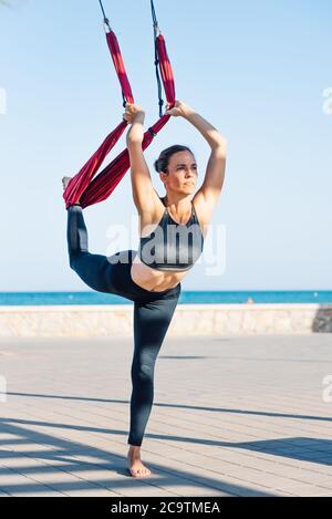 jeune femme faisant du yoga à l'extérieur sur la promenade du bord de mer, en utilisant l'oscillation