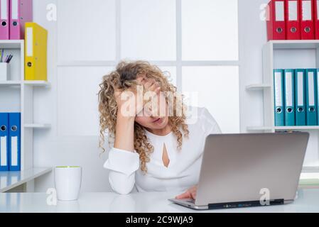 Employé de bureau fatigué. Femme paresseuse s'ennuyant avec un ordinateur portable le matin, ennuyeuse au bureau. Banque D'Images