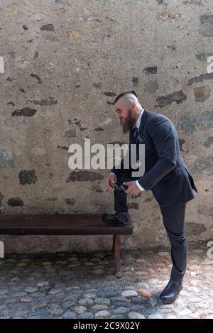 Homme dans des vêtements élégants repose un pied sur un banc en bois dans un petit village