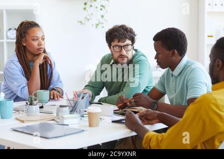 Portrait d'un responsable mûr barbu qui parle à une équipe d'affaires multiethnique tout en discutant des plans pendant la réunion au bureau, dans l'espace de photocopie Banque D'Images