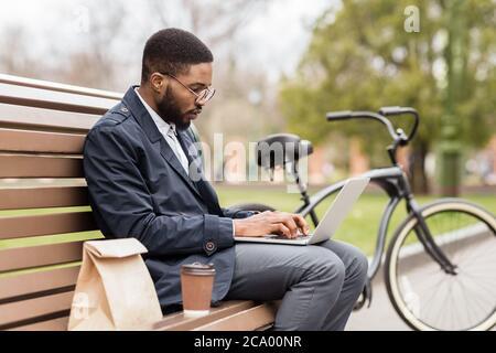 Beau directeur travaillant sur ordinateur portable dans le parc au printemps