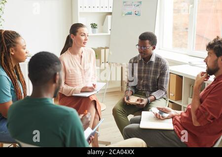 Groupe multiethnique de personnes assis en cercle tout en discutant de la stratégie pour le projet d'entreprise au bureau, se concentrer sur la femme leader parlant à des collègues, espace de copie