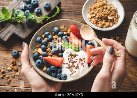 Manger du granola avec du yaourt grec et des baies. Les mains des femmes tiennent un bol de céréales de petit déjeuner saines granola avec des fruits et du yaourt. Concept de nettoyage