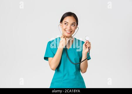 Covid-19, les professionnels de la santé et la prévention du virus concept. Souriant mignon asiatique médecin, infirmière femme examiner les poumons du patient, à l'aide du stéthoscope, à l'écoute Banque D'Images