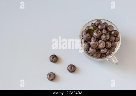 Bleuets frais dans un bol transparent. Bleuets frais sur table bleue. Concept de saine alimentation et nutrition. Vue de dessus. Copier l'espace. Banque D'Images