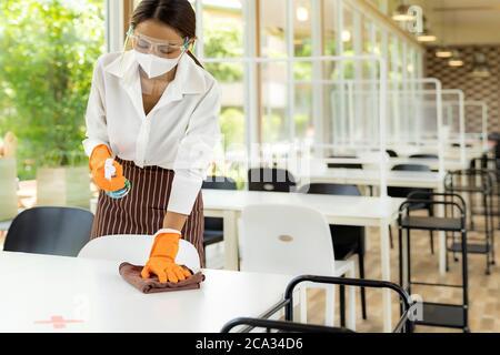 Portrait attirante serveuse asiatique porter un masque et un écran facial nettoyer la table avec de l'alcool et un chiffon humide avant d'accueillir le client. Nouvelle normale Banque D'Images