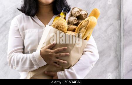 Gros plan asiatique sourire femme maison tenant le pain variété dans sac en papier jetable sur fond gris vintage loft. Boulangerie alimentation et boissons épicerie