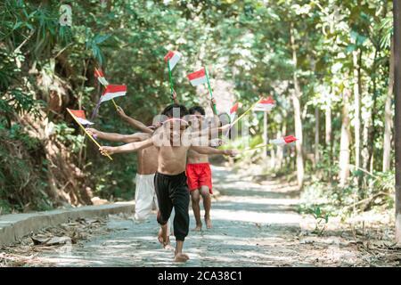 avoir un groupe amusant d'enfants courir sans vêtements pourchassant chacun autre lorsque vous tenez le petit drapeau rouge et blanc et a soulevé le drapeau sur un fond d'arbre