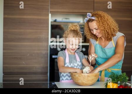 Joyeux cacaucasien maman et fille préparant la boulangerie ensemble, la cuisine de pizza et de s'amuser dans la cuisine. Couple aimant embrassant, embrassant avec ha