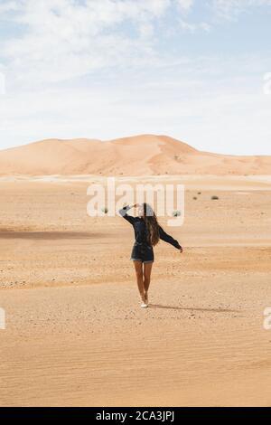 Femme marchant dans un magnifique désert avec des dunes de sable à l'horizon. Voyage au Maroc, Sahara, Merzouga. Concept de liberté et de voyage.