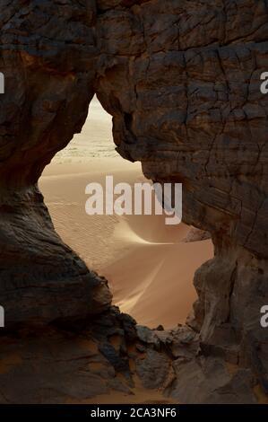 Algérie, Illizi, Parc national de Tassili n'Ajjer : dunes de sable, vue à travers un craque naturel de roche à Wadi à Djeran des montagnes de Tadrarart.